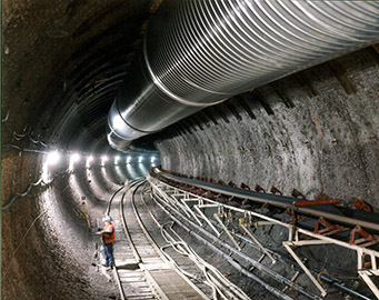VIEW OF AN EXPLORATORY TUNNEL DUG BY THE 25-FOOT-DIAMETER TUNNEL BORING MACHINE AT YUCCA MOUNTAIN.
