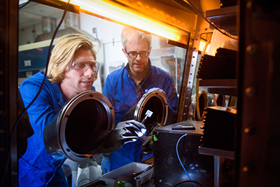 Stanford postdoctoral scholar Tomas Leijtens and Professor Mike McGehee examine perovskite tandem solar cells.