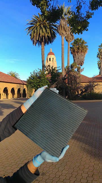 student holding produced module inside Stanford quad