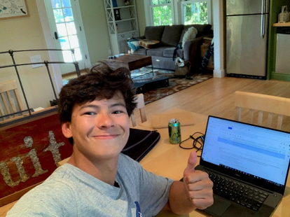 Austin Stack giving a thumbs up in front of a laptop