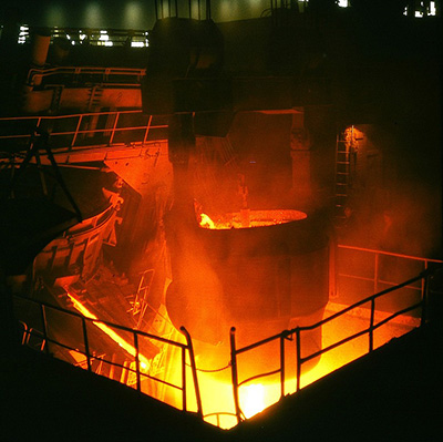 Vessel of molten iron above large, flaming furnace.