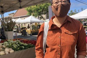 Woman with dark hair wearing a mask in front of a farmers' market