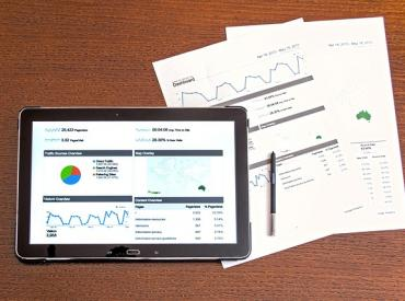 Tablet with graphs next to paper with graphs