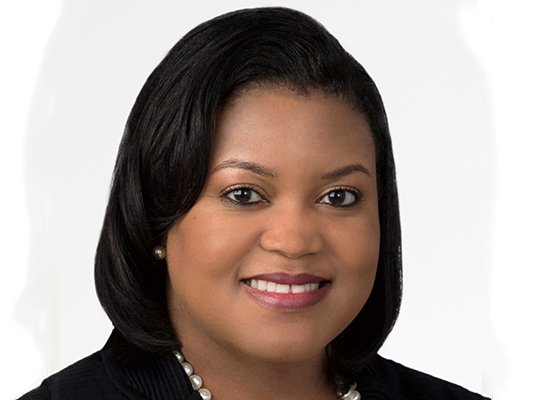 headshot of Colette Honorable: she's a Black woman with shoulder length hair. She is looking at the camera, smiling, and is wearing a black blouse or jacket with pearls.