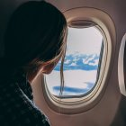 Woman looking out airplane window to blue sky with clouds