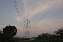 Pylon against blue and pink sky with trees below