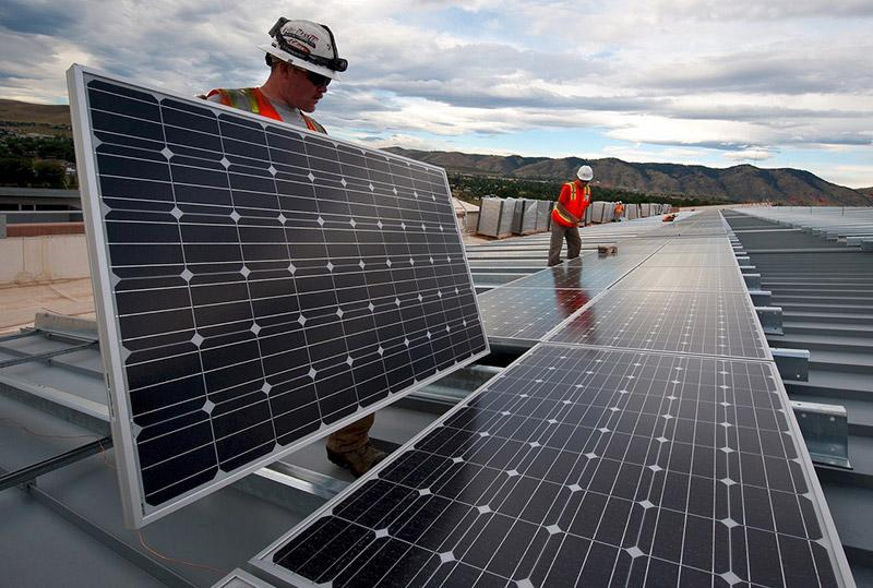 Two men working on installing solar panels on rooftop with mountain in the far background