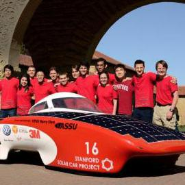 Students standing with solar car on Stanford campus