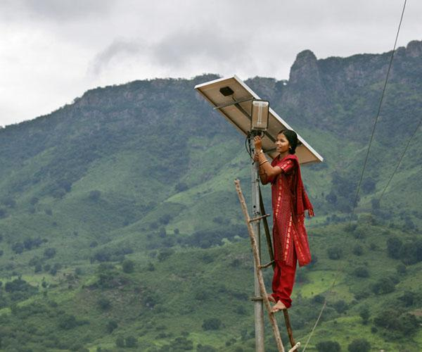 A woman at the top of a single solar panel in a rural mountainous area