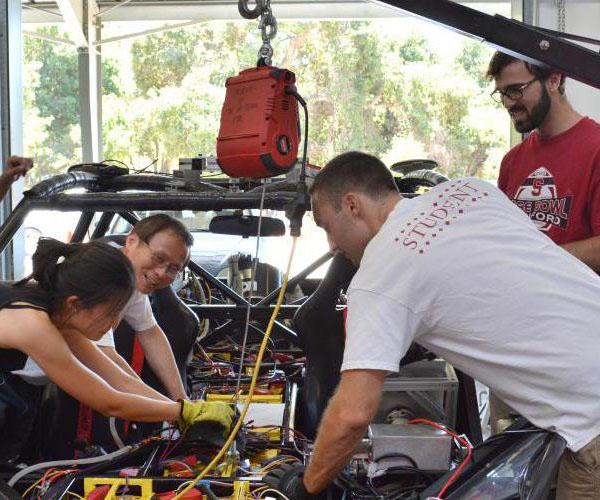 Researchers working under the hood of a car