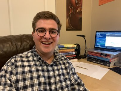 Portrait of Matthew Dardet sitting in front of a desk with laptop