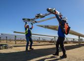 Workers at a solar station attach the robot that cleans the panels. Jobs like these are increasing rapidly as the nation moves to sustainable energy sources.