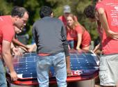 Members of the Stanford Solar Car Project carefully install the solar-paneled top shell of their new car named Sundae.