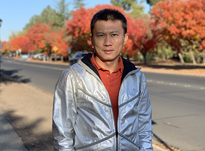 Yi Cui wearing a silver-colored jacket outside